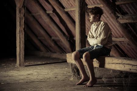 Barefoot tiener geïmmobiliseerd in een rechte jas zittend op een houten balk bedekt met spinnenwebben in een schaduwrijke zolder in een conceptueel atmosferisch beeld met kopie ruimte