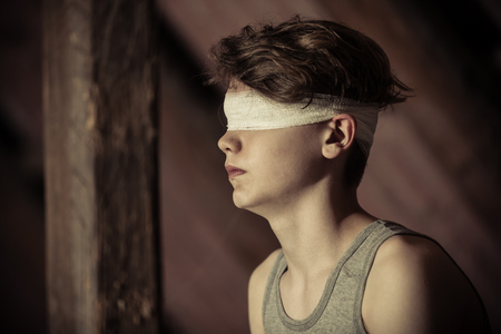 Teenage boy tied up in a blindfold sitting in an attic in the darkness in a conceptual image of abuse and hostage taking Foto de archivo