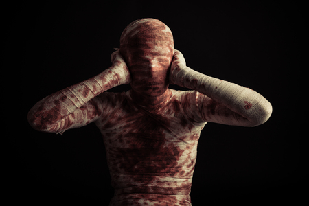 Front view on single bloody mummy with hands on hears over black background for scary Halloween scene Stock Photo
