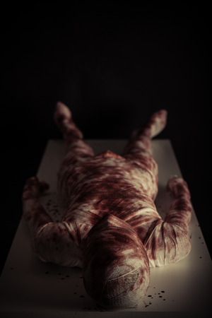 ghoulish: Bloody gauze covered young mummy in darkness displayed on light colored table