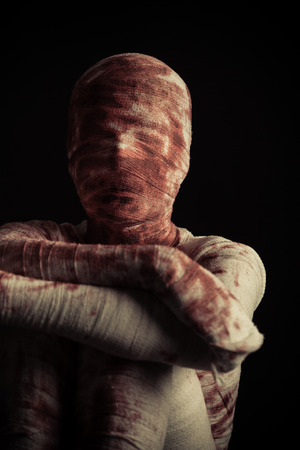 Creepy blood spattered mummy sits in darkness with arms crossed and resting on his knees