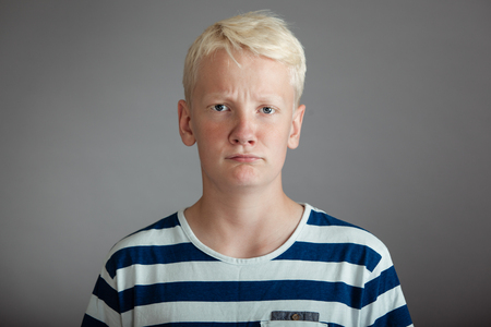 puzzlement: Front view on blond boy dressed in blue and white shirt with puzzled expression over gray background
