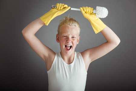 Excited screaming single blond boy in white undershirt and yellow gloves holding toilet scrubber brush above his head