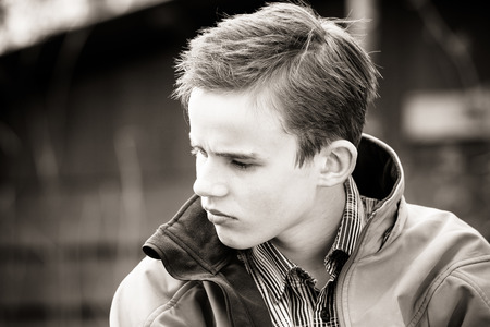Black and white image of frowning boy in jacket seated outdoors on clear day