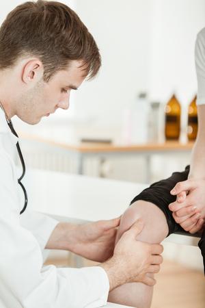 若者の深刻な男性医師または理学療法士診療所で検査のベッドの上に座って若い 10 代の少年の膝を調べる 写真素材