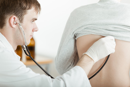 Close Up of Young Teenage Boy with Lifted Shirt During Check Up in Doctor Office During Examination While Doctor Listens to Heart Rate on Back with Stethoscope
