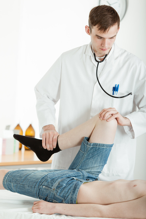 Young Male Doctor Examining Mobility and Flexibility of Knee and Leg of Young Teenage Boy Who is Lying on Table in Clinic Office Stock Photo