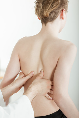 Rear View of Young Shirtless Teenage Boy Sitting in Clinic with Doctor or Therapist Giving Patient Massage or Examining Muscle Back Pain