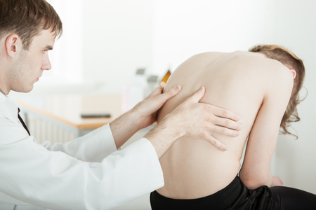 Rear View of Young Male Doctor Examining Sore Back Muscles of Young Teenage Boy Sitting Shirtless and Slumped Over on Table in Doctor Clinic