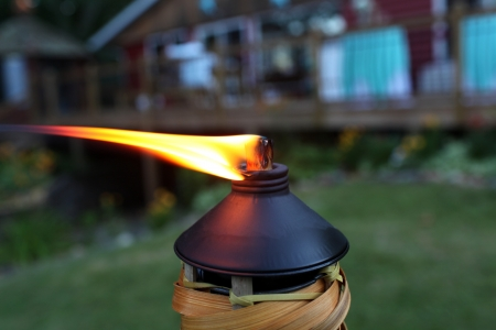 Tiki torch burning at an outdoor party. photo
