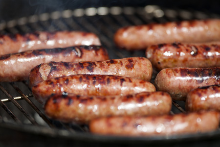 bratwurst: Hot dogs on the grill. Stock Photo