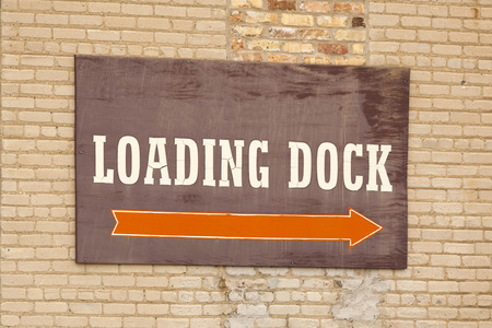 Weathered loading dock sign on a brick wall.