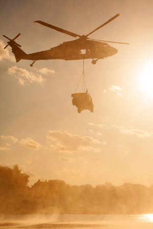 A UH-60 Blackhawk helicopter carries a humvee over a river at sunset.