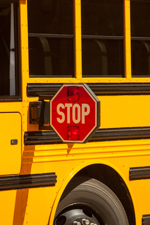 Yellow school bus stop sign up close view.