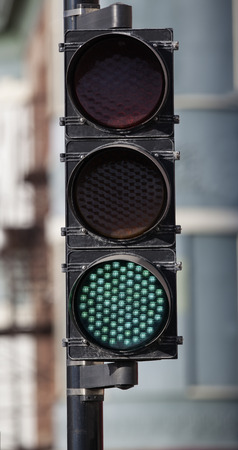 highroad: Green traffic light up close in the city.