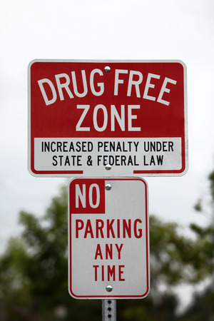 posted: Drug free zone sign and no parking sign posted in a city park.