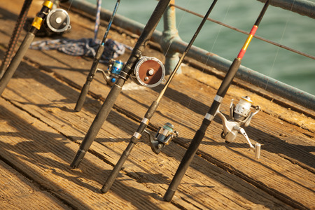 wooden dock: Fishing reels resting on a wooden dock. Stock Photo