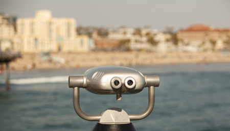 two visions: Scenic beach view from binoculars mounted on a pier.