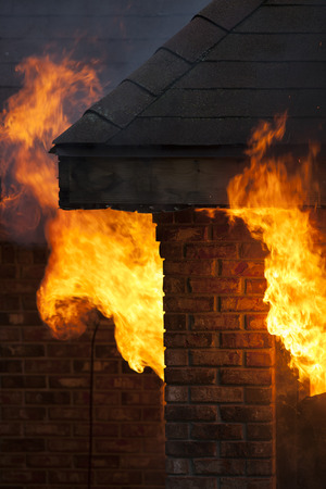 house on fire: A residential house in flames during a fire disaster. Stock Photo