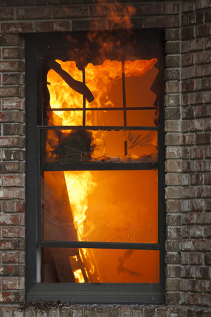 residential building insurance: A fire burns inside a residential home.
