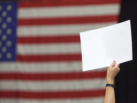 protestor: A woman holds up a political sign in front of an American flag. Stock Photo