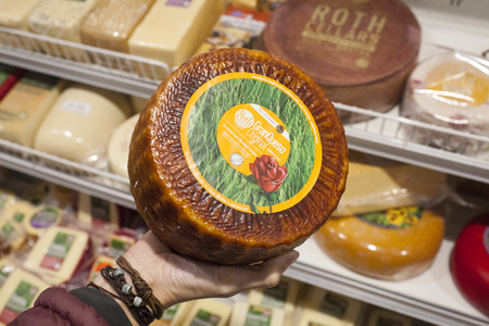 roth: MONROE, WIUSA - December 23, 2016: A woman holds a wheel of Emmi Roth GranQueso Original cheese. The Emmi Roth cheesemakers recently won grand prize for their Roth Grand Cru Surchoix, which is a hard smear-ripened cheese. Editorial