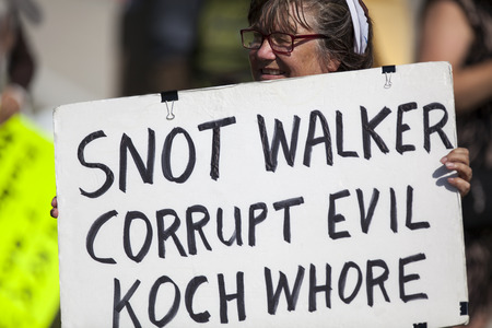 WAUKESHA, WI/USA - July 13, 2015: A woman holds a protest sign in front of the Waukesha Convention Center in Waukesha, Wisconsin where Governor Scott Walker is about to make an annoucement that he will run for President in the 2016 United States President