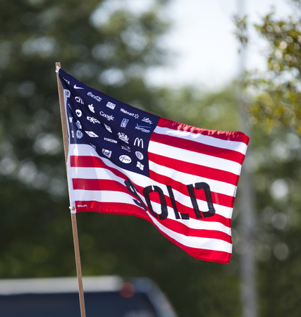 protestor: WAUKESHA, WIUSA - July 13, 2015: A flag protesting corporate spending in American political elections in front of the Waukesha Convention Center during a progressive political protest.