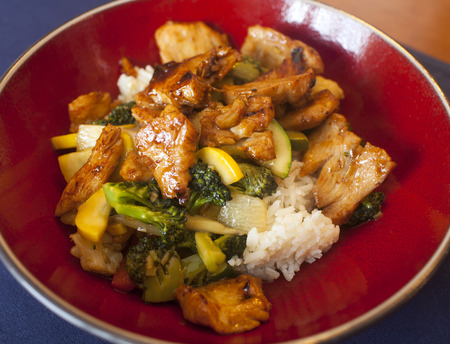 broccolli: Chicken and vegetable stir fry up close on a red plate.