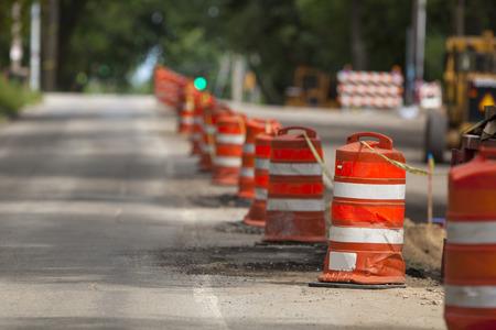 Zona de la construcción con marcadores de precaución naranjas a lo largo de una calle urbana.