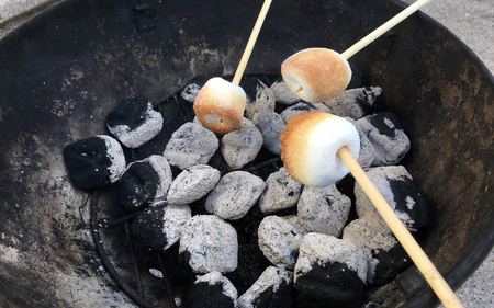 Roasting marshmallows over coals to make s'mores dessert.