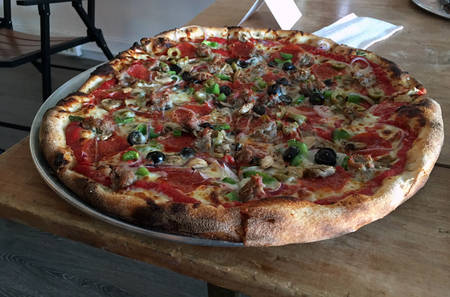 woodfire: A wood fire grilled supreme pizza with pepperoni, olives, sausage and peppers. Stock Photo