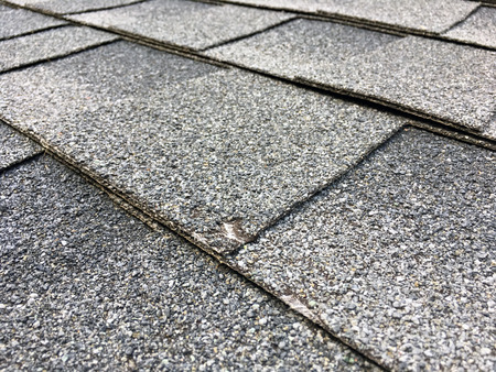 Asphault shingles with a small  big of a hail damage up close.