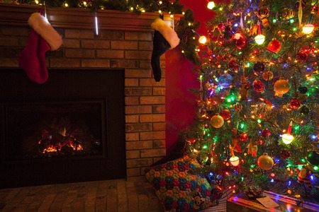 Christmas fireplace with stockings and Christmas tree and gifts. Stock fotó