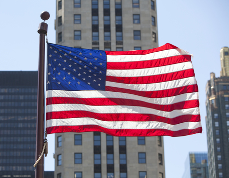 An American flag flying over a United States city.