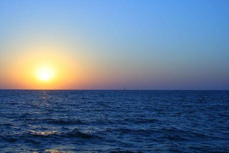 Coucher du soleil rouge et orange au-dessus de la mer.
