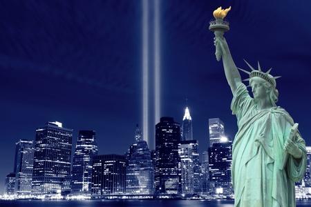 夜にマンハッタンのスカイライン、ライトの塔、自由の女神像を下げる