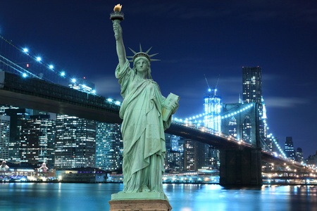 manhattan skyline, brooklyn bridge and the statue of liberty at night lights, new york city