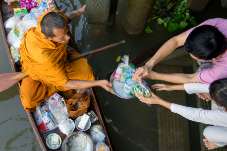Amphawa, Thailand. October 25, 2015. Monk receiving morning Alms in Amphawa from a worshiper.