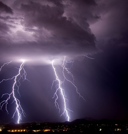 Thundershower and lightning over city and mountains photo