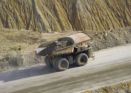A large truck hauls a load of ore in an open pit copper mine