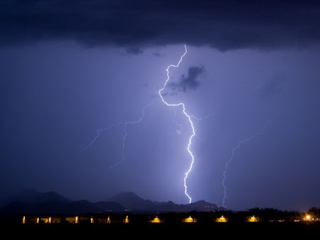thundershower: Lightning with airplane hangers in the foreground Stock Photo