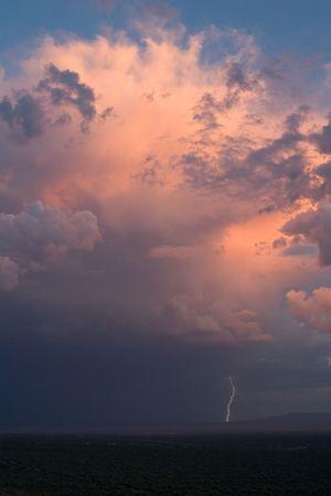 thunderhead: Large thundershower, illuminated by the setting sun, with cloud-to-ground lightning strike Stock Photo