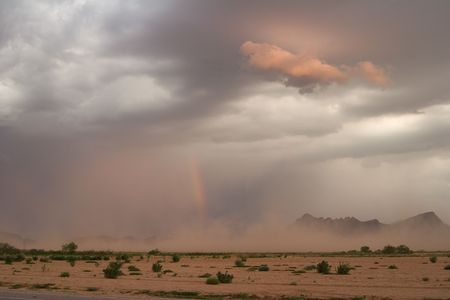 Desert dust storm, or haboob, with rainbow at sunset