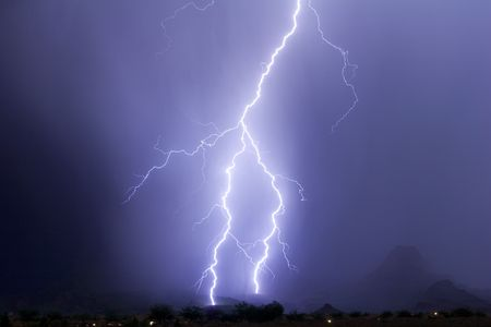 clearly: Lightning bolt clearly hitting two foothills near a mountain peak Stock Photo