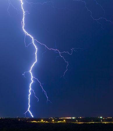striking: Lightning striking a small hill.