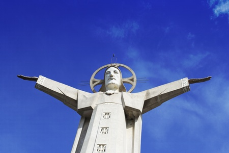 a statue of Jesus at the top of the hill photo