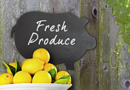 Fresh Bowl Of Lemons & Black Chalkboard Pig Restaurant Menu Advertising Space For Fresh Citrus Fruit Produce Over Distressed Grunge, Vintage, Aged And Green Moss Covered Wood Background Framed With Grape Leaves And Tendrils photo