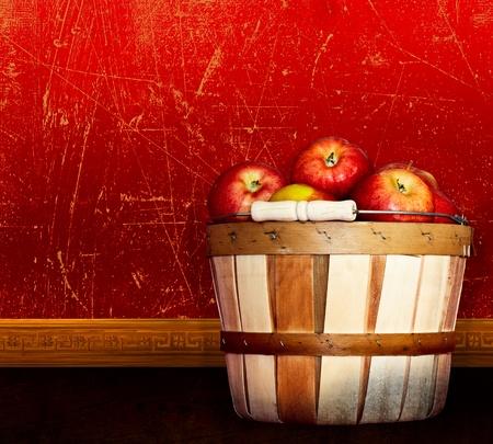 Cesto di mele Red Delicious e Pink Lady sane ~ Muro vintage di Grunge color rosso antico, con texture e angosciata, Parapetto decorativo e pavimento in legno massello decorativo Archivio Fotografico - 11550384