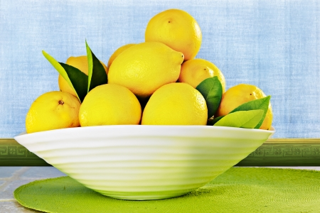 Eureka Lemons in a White China Bowl Sitting On Kitchen Counter ~ Background Is Textured Plaster Wall with Blue Sponge Antiqued Grunge Faux Paint Treatment Archivio Fotografico